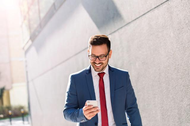 Handsome smiling young businessman reading text message on his phone