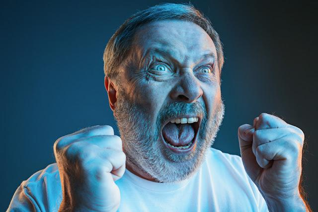 Screaming, hate, rage. Crying emotional angry man screaming in colorful bright lights at studio background. Emotional, mature face. male half-length portrait. Human emotions, facial expression concept