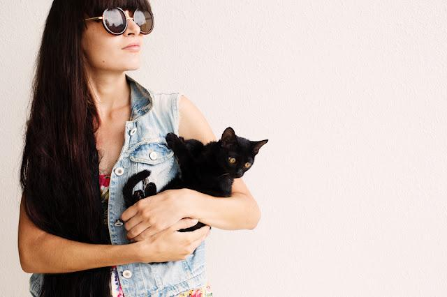 Long black hair fashion girl in sunglasses holding little black cat on white wall background