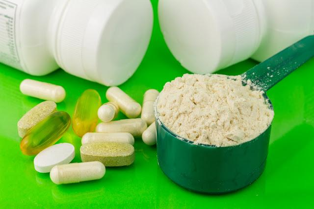Mixed natural food supplement pills and protein powder in plastic spoon on green background
