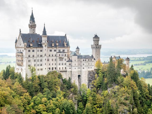 Neuschwanstein castle is the most famous beautiful castle in Germany, inspiration for Disneylands sleeping beauty castle, located on Alpine foothills, under cloudy sky