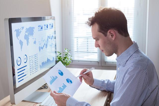 Investor analyzing financial reports and key performance indicators (KPI) of stock market on the computer screen with business intelligence (BI) analytics and graphs at the office