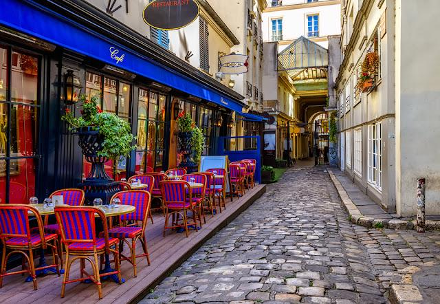 Typical view of the Parisian street with tables with tables of cafe in Paris, France. Architecture and landmark of Paris. Cozy Paris cityscape