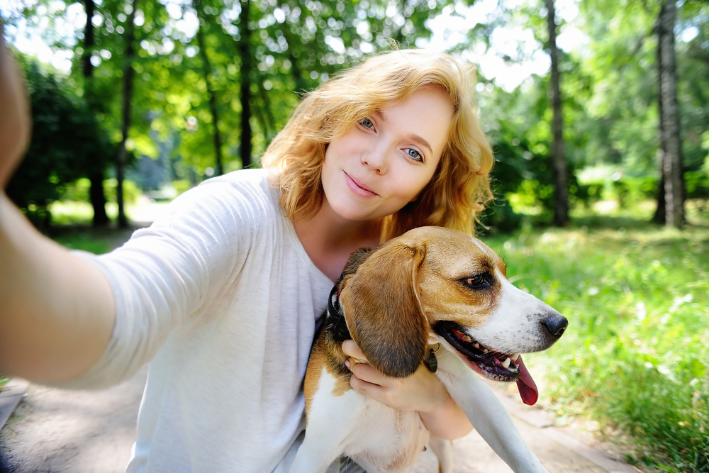 Young beautiful hipster woman making selfie photo with Beagle dog using her mobile phone