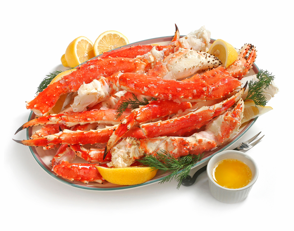 Alaskan King Crab legs on platter, served with lemon and butter, on white background